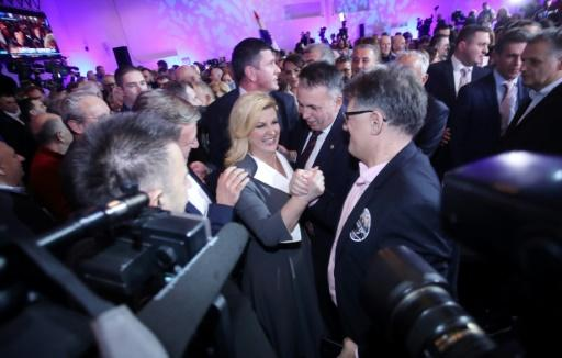 Incumbent president and candidate of the Croatian Democratic Union (HDZ) party Kolinda Grabar-Kitarovic (C) is congratulated by fellow party members after she made it into the second round of the election to be held January 5