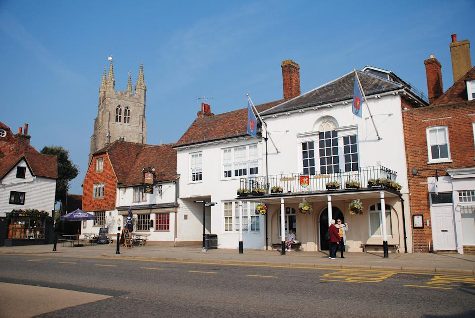 Tenterden, England - April 17, 2019: People stand by the historic Town Hall at Tenterden in Kent. The building dates from 1790. The Woolpack pub and hotel stands next door.