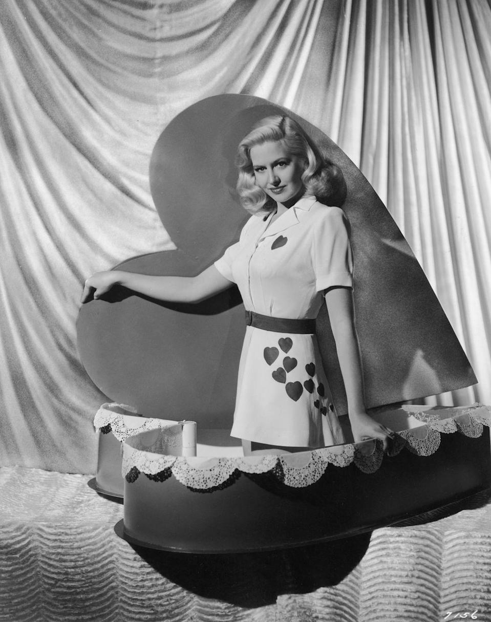 <p>Surprise! It's actress Marilyn Maxwell just casually popping out of a heart-shaped box for the occasion. </p>