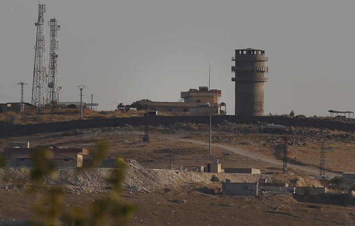 In this photo taken from the Turkish side of the border between Turkey and Syria, in Suruc, southeastern Turkey, a U.S forces outpost is seen on a hilltop outside Ayn Al Arab or Kobani, Syria, Saturday, Oct. 12, 2019. U.S. officials say an American outpost in northeastern Syria has been vacated after coming under fire from Turkish artillery. The officials say a number of U.S. troops left their post on a hill outside the town of Kobani after it came under fire. Turkey says it didn't target the U.S. outpost but was responding to fire from Kurdish groups nearby. (AP Photo/Emrah Gurel)