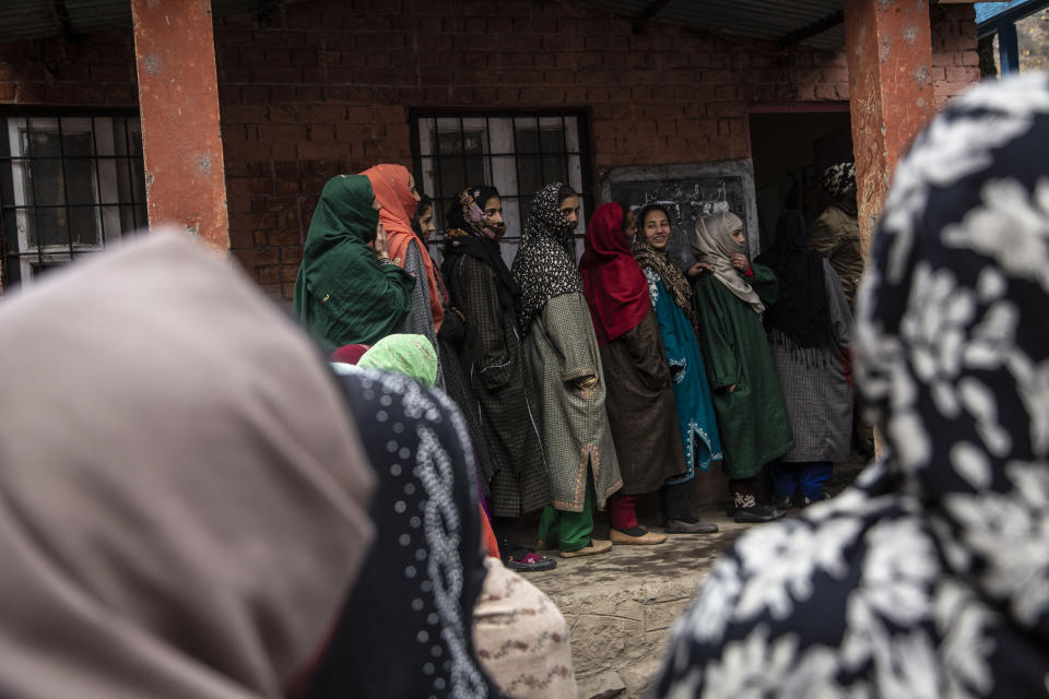 Kashmiris wait in a queue to cast their votes during the first phase of District Development Councils election on the outskirts of Srinagar, Indian controlled Kashmir, Saturday, Nov. 28, 2020. Thousands of people in Indian-controlled Kashmir voted Saturday amid tight security and freezing cold temperatures in the first phase of local elections, the first since New Delhi revoked the disputed region's semiautonomous status. (AP Photo/Mukhtar Khan)