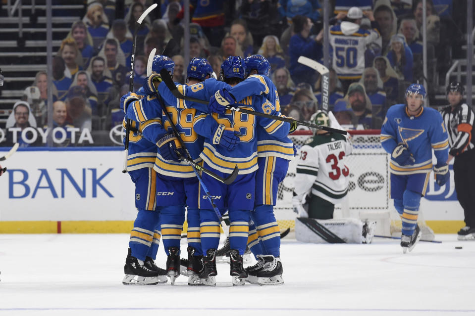 St. Louis Blues' Mike Hoffman (68) is congratulated by teammates after scoring the tying goal against the Minnesota Wild during the third period of an NHL hockey game on Saturday, April 10, 2021, in St. Louis. (AP Photo/Joe Puetz)
