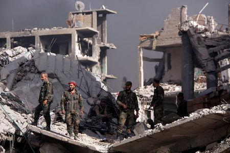 Syrian army soldiers stand on the rubble of damage buildings in al Hajar al-Aswad Syria