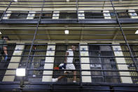 FILE - In this Aug. 16, 2016, file photo, a condemned inmate walks along the east block of death row at San Quentin State Prison in San Quentin, Calif. The California Labor and Workforce Development Agency confirmed Tuesday, Dec. 1, 2020, that California has sent about $400 million in unemployment benefits to state prison inmates. In all records show 31,000 inmates have applied for benefits and about 20,800 were paid $400 million. A group of local and federal prosecutors said 133 inmates on death row were named in claims. (AP Photo/Eric Risberg, File)
