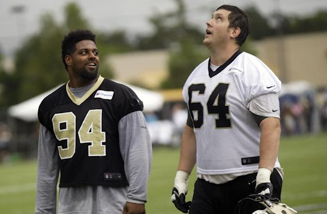 FILE - In this photo taken June 10, 2014, New Orleans Saints tackle Zach Strief (64) looks up at rain clouds as he walks off the field with defensive end Cameron Jordan (94) after minicamp at their NFL football training facility in Metairie, La. Coming off his first Pro Bowl, Jordan feels eve better about his upcoming fourth season with the Saints. (AP Photo/Gerald Herbert, File)
