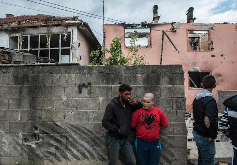 A young boy wearing a T-shirt with the colours of the Albanian flag stands next to a destroyed house after fighting in Kumanovo on May 11, 2015 (AFP Photo/Armend Nimani)