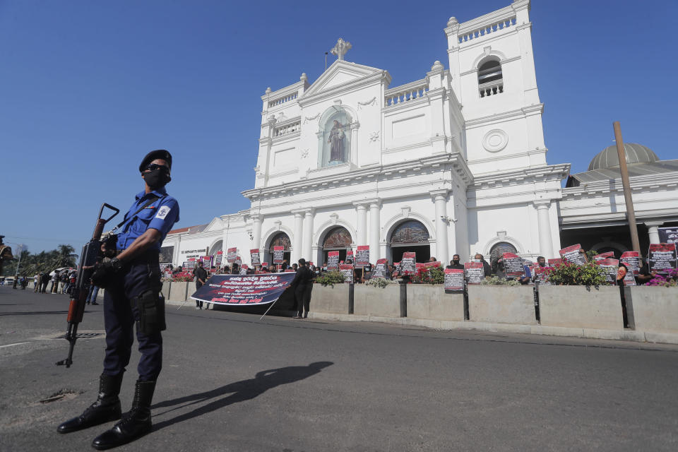 A policeman guards as Catholic devotees hold placards during a protest demanding justice for the 2019 Easter Sunday bomb attack victims out side the St. Anthony's church, one of attack sites, in Colombo, Sri Lanka, Sunday, March 7, 2021. (AP Photo/Eranga Jayawardena)