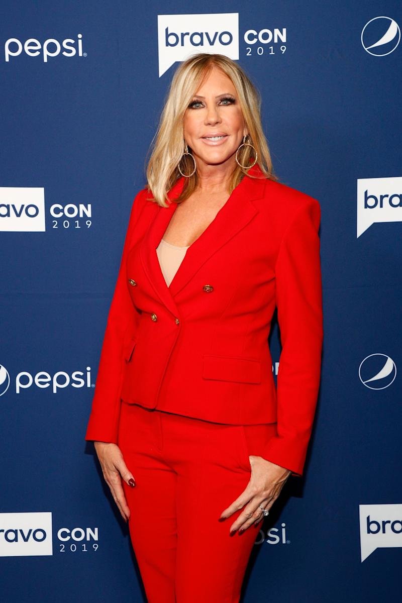 Vicki Gunvalson poses on the Bravo Con red carpet wearing a red pantsuit