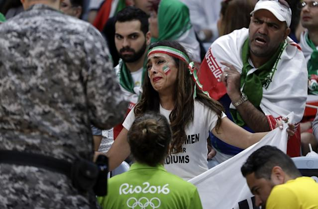 "A woman is confronted by Olympic officials for holding a sign that reads, ""Let Iranian Women Enter Their Stadiums."" (AP)"