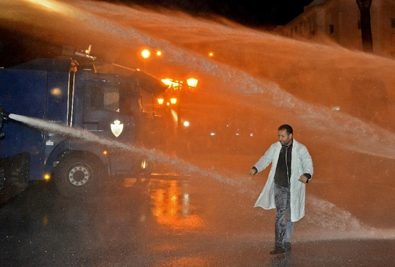 A Moroccan teacher walks through a water cannon during a demonstration calling for permanent contracts