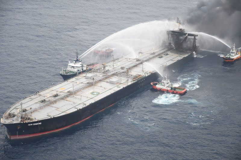 A Sri Lankan Navy boat sprays water on the New Diamond, a very large crude carrier (VLCC) chartered by Indian Oil Corp (IOC), that was carrying the equivalent of about 2 million barrels of oil, after a fire broke out off east coast of Sri Lanka