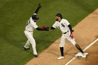 Chicago White Sox's Billy Hamilton, right, celebrates his RBI triple off Minnesota Twins starting pitcher J.A. Happ with third base coach Joe McEwing during the first inning of a baseball game Wednesday, May 12, 2021, in Chicago. (AP Photo/Charles Rex Arbogast)