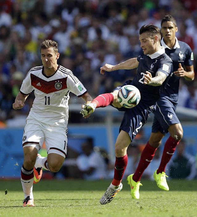 France's Mathieu Debuchy clears the ball ahead of Germany's Miroslav Klose during the World Cup quarterfinal soccer match at the Maracana Stadium in Rio de Janeiro, Brazil, Friday, July 4, 2014. (AP Photo/Kirsty Wigglesworth)