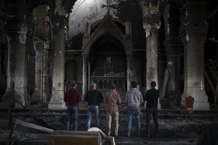 FILE - In this Nov. 12, 2016 file photo, Iraqi Christians pray at the Church of the Immaculate Conception, damaged by Islamic State fighters during their occupation of Qaraqosh, east of Mosul, Iraq. Iraq was estimated to have more than 1 million Christians before the 2003 U.S.-led invasion that toppled dictator Saddam Hussein. Now, church officials estimate only few hundred remain within Iraq borders. The rest are scattered across the globe, resettling in far-flung places like Australia, Canada and Sweden as well as neighboring countries. (AP Photo/Felipe Dana)