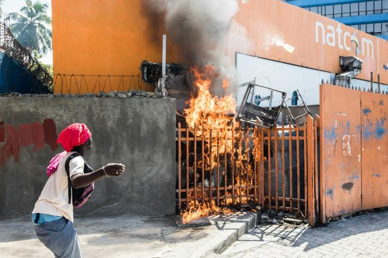 A man watches a fire as protesters, medical professionals and political opponents demonstrate in Port-au-Prince on October 30