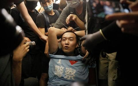 "Protesters surround a man carrying a t-shirt baring the words ""I love police"" who protesters claimed was a police officer from mainland China - Credit: AP"
