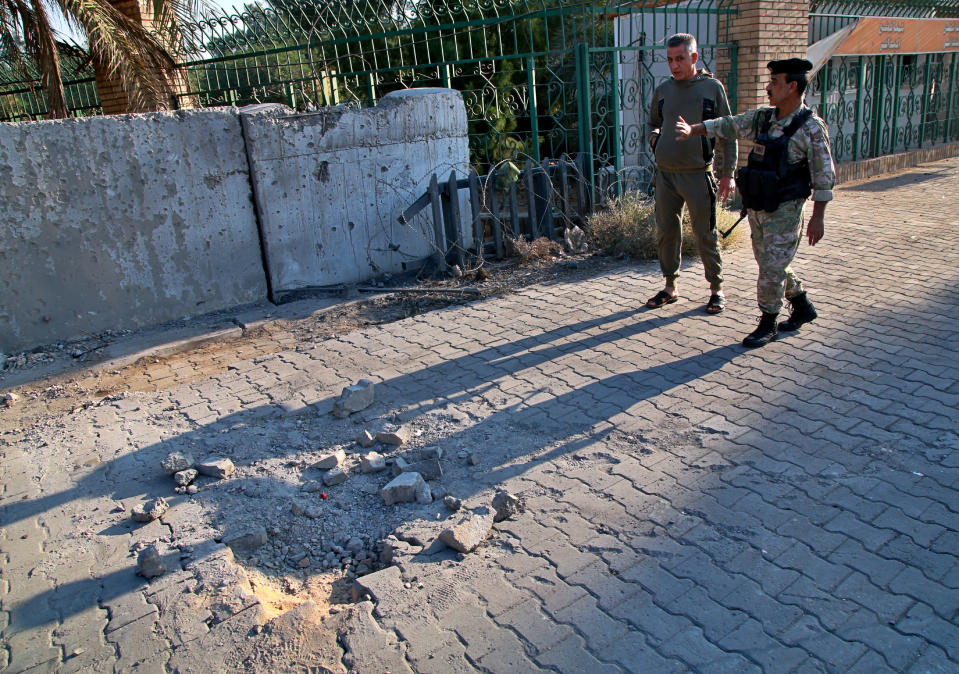 Security forces inspect the scene of the rocket attack at the gate of al-Zawra public park in Baghdad, Iraq, Wednesday, Nov. 18, 2020. Rockets struck Iraq's capital on Tuesday with four landing inside the heavily fortified Green Zone, Iraq's military said, killing a child and wounding at least five people, signaling an end to an informal truce announced by Iran-backed militias in October. (AP Photo/Khalid Mohammed)