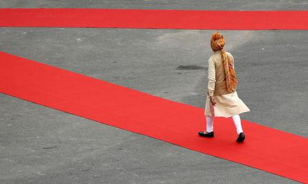 Indian Prime Minister Modi walks to inspect a guard of honour upon his arrival at the historic Red Fort during Independence Day celebrations in Delhi