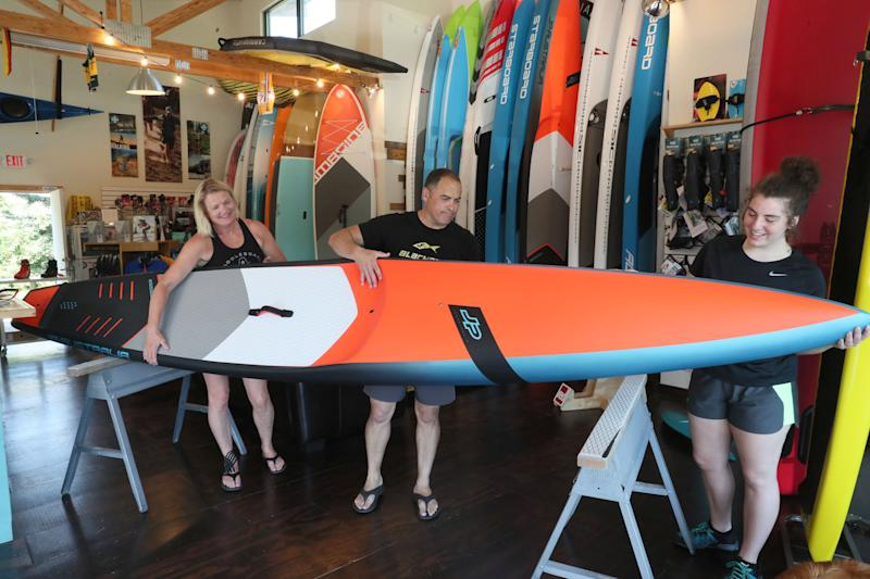 Paddleboard Specialists owners Cris Rosario and his wife, Susanna, assisted by their daughter Sophia, check over a new 14-foot race paddleboard before putting it on display.