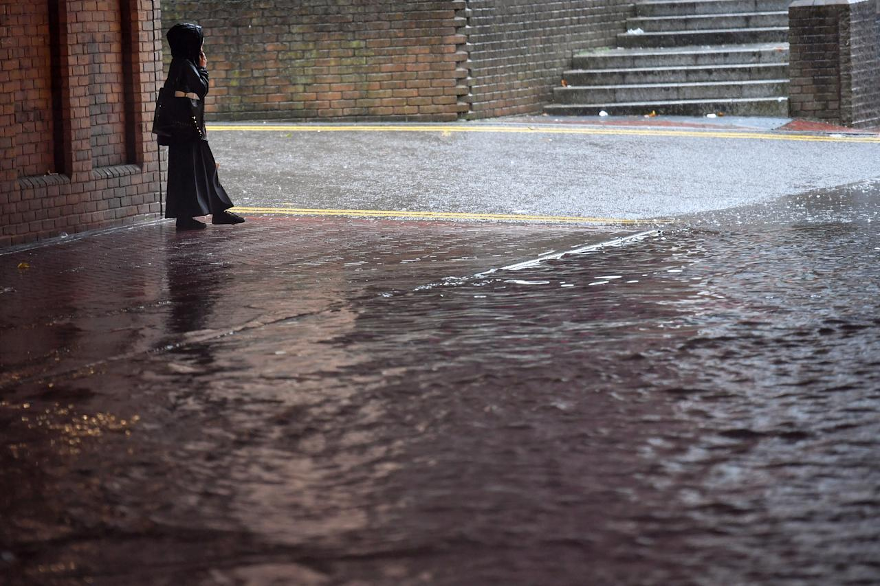 A pedestrian walks past a flooded road in Birmingham city centre. (PA)