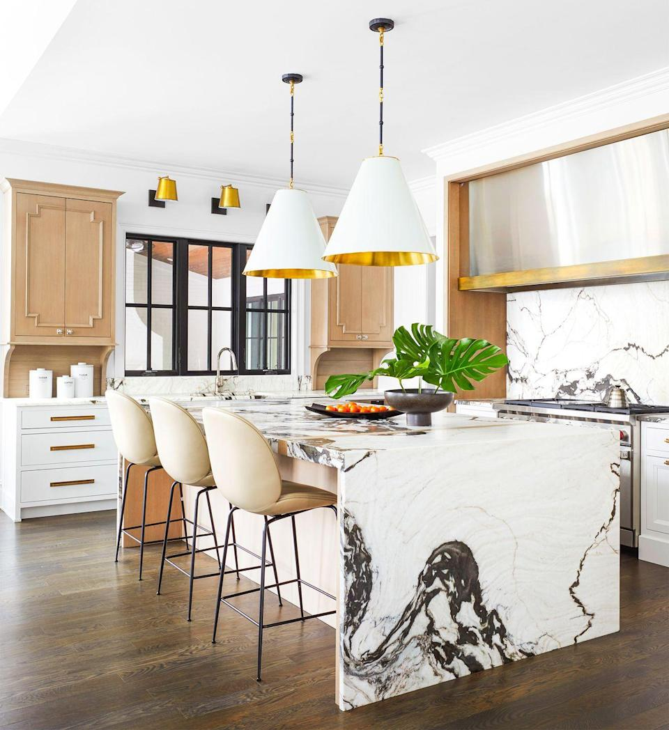 "<p>In this kitchen designed by Corey Damen Jenkins, the wood tones, brown marble swirls, and beige bar stools warm up the crisp white staples while the metallic accents add some glam. Jenkins says the granite ""was a bit of a sell. I told the clients to look at it as art. Of course, now it's their favorite thing.""</p>"