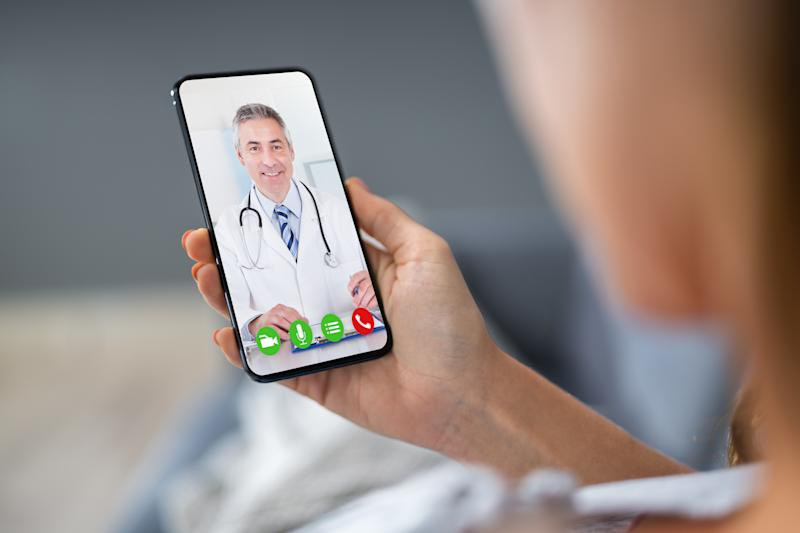 Person Videochatting With Doctor On Mobile Phone