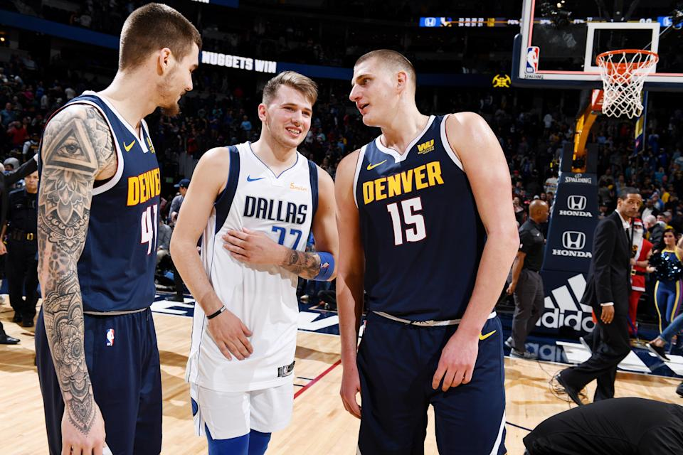 Luka Doncic shares a moment with Nuggets Juan Hernangomez (L) and Nikola Jokic on Tuesday in Denver. (Getty Images)