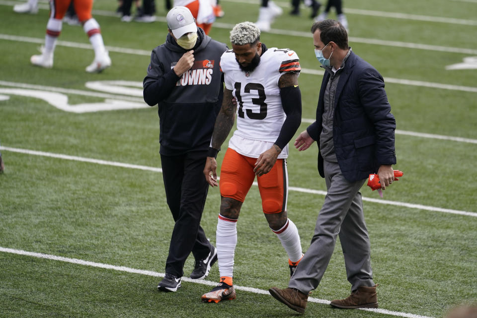 CORRECTS TO FIRST HALF - Cleveland Browns wide receiver Odell Beckham Jr. (13) is helped off the field in the first half of an NFL football game against the Cincinnati Bengals, Sunday, Oct. 25, 2020, in Cincinnati. (AP Photo/Michael Conroy)
