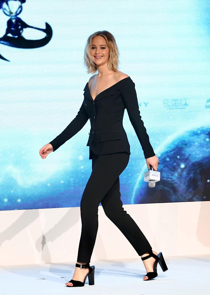 <p>Jennifer Lawrence wore a black off-the-shoulder Antonio Berardi blazer with tapered pants and sandals during a promotional event for 'Passengers' in Beijing, China. The double-breasted blazer featured a plunging neckline, so she kept her accessories simple, wearing just a silver necklace. Like many other appearances, she styled her hair in loose waves. (Photo: Splash News) </p>