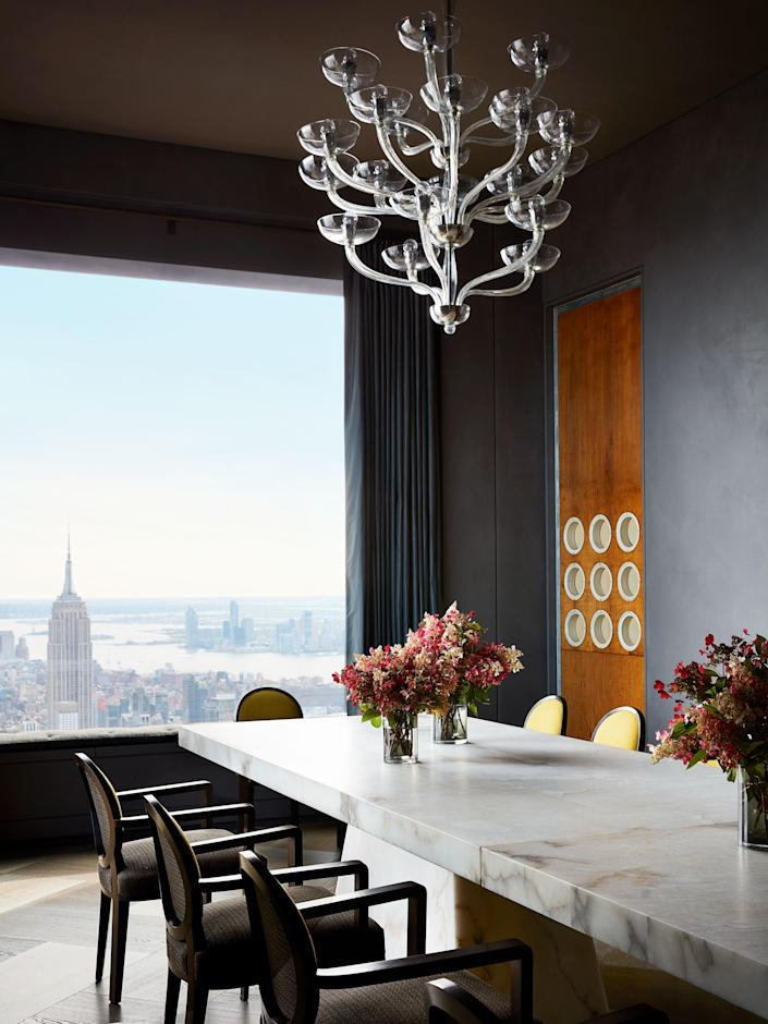 In the dining room, Jean Royère armchairs surround an alabaster table by Rick Owens from Carpenters Workshop gallery. Curtains of Lisio silk taffeta, Seguso chandelier, and door panel with portholes by Jean Prouvé.