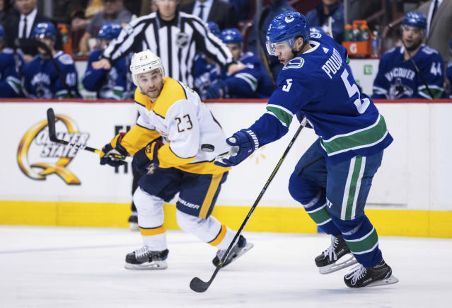 Vancouver Canucks' Derrick Pouliot (5) reaches for the puck in front of Nashville Predators' Rocco Grimaldi (23) during the first period of an NHL hockey game Thursday, Dec. 6, 2018, in Vancouver, British Columbia. (Darry Dyck/The Canadian Press via AP)