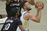 Golden State Warriors' Stephen Curry, right, goes to the basket against Cleveland Cavaliers' Darius Garland (10) in the second half of an NBA basketball game, Thursday, April 15, 2021, in Cleveland. (AP Photo/David Dermer)