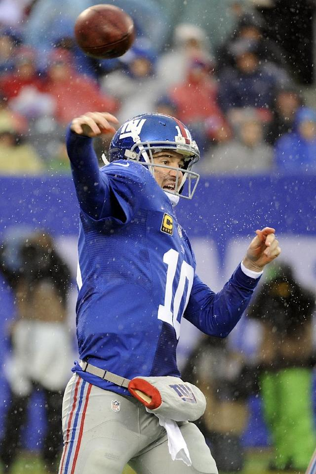In the rain, New York Giants quarterback Eli Manning (10) throws a pass during the first half of an NFL football game against the Washington Redskins, Sunday, Dec. 29, 2013, in East Rutherford, N.J. (AP Photo/Bill Kostroun)