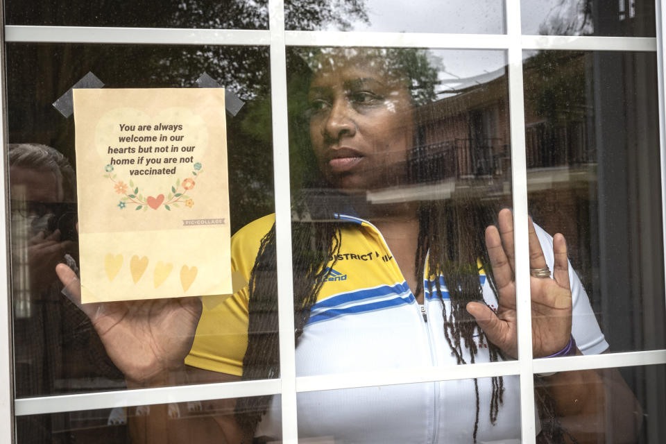 """Octavia Tokley, the widow of Erin """"Toke"""" Tokley, a Philadelphia cop who died from COVID-19 in March poses on Aug. 29, 2021, in Secane, Pa. Tokley was scheduled to be vaccinated on March 11 – which turned out to be his funeral. (AP Photo/Laurence Kesterson)"""