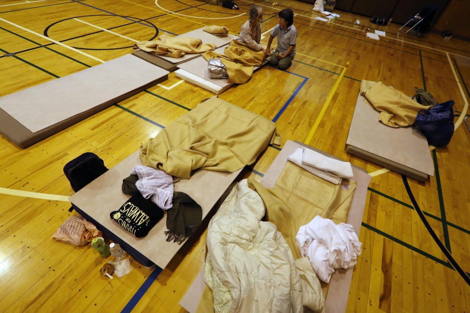 Evacuees from Typhoon Hagibis take shelter at a nearby elementary school gym on Monday, Oct. 14, 2019, in Kawagoe City, Japan. Rescue crews are digging through mudslides and searching near swollen rivers for missing people after Hagibis caused serious damage in central and northern Japan. (AP Photo/Eugene Hoshiko)