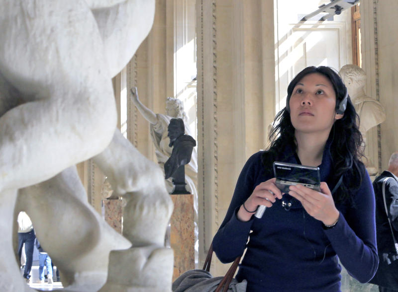A visitor views a sculpture at the Louvre Museum in Paris with the help of the new audio guide, Thursday April 12, 2012. The famed Paris museum is going 3D visual with its electronic guides in a deal with Japan's Nintendo to provide game consoles to help visitors who navigate its labyrinthine halls by the millions each year. The guides, in seven languages, and accompanying headsets cost Euro5 ($6.50) on top of the museum's Euro10 standard admission price. (AP Photo/Jacques Brinon)