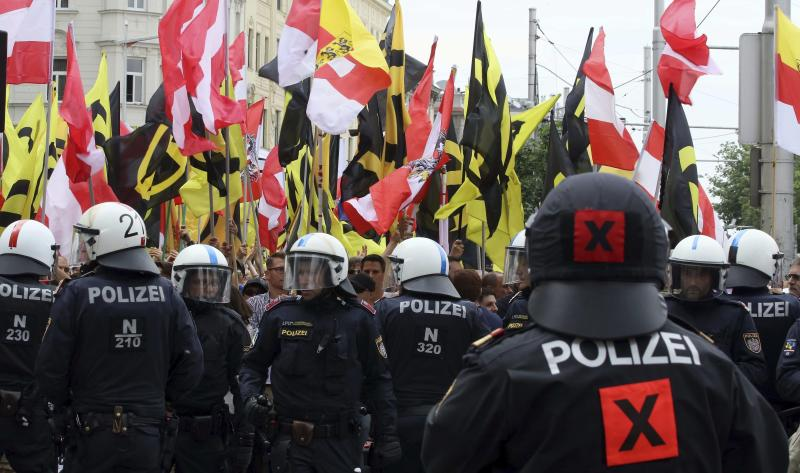 FILE - In this June 11, 2016 file photo police forces stand in front of demonstrators during a rally of the group Austrian protesters against migrants in Vienna, Austria. Austria was among the first countries in Europe to put out the welcome mat to migrants when the first waves of people fleeing war and poverty reached the continent. Now, its focus is showing them the door. Parliament is set to pass a law stripping denied asylum-seekers of pocket money, food and shelter, potentially leaving them on the street. (AP Photo/Ronald Zak, file)