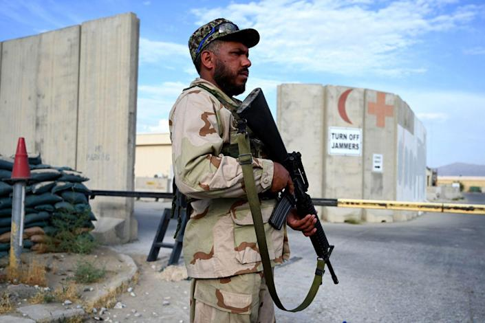 Armed Afghan soldier stands guard at a gate