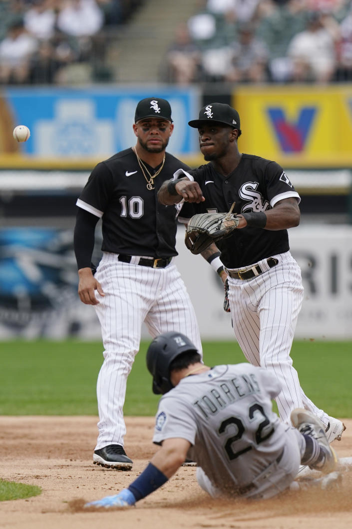 Chicago White Sox third baseman Yoan Moncada, left, watches as shortstop Tim Anderson, right, throws out Seattle Mariners' Jake Fraley at first after forcing out Luis Torrens (22) at second during the third inning of a baseball game in Chicago, Saturday, June 26, 2021. (AP Photo/Nam Y. Huh)