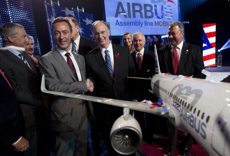 Airbus President & CEO Fabrice Bregier, second from left, shakes hands with Alabama Gov. Robert Bentley as they pose with a model of the A320 Airbus following an announcement that Airbus will establish its first assembly plant in the United States in Mobile, Ala., Monday, July 2, 2012. The French-based company said the Alabama plant is expected to cost $600 million to build and will employ 1,000 people when it reaches full production, likely to be four planes a month by 2017. (AP Photo/Dave Martin)