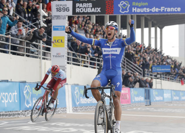 Philippe Gilbert of Belgium celebrates as he crosses the finish line ahead of Nils Politt of Germany, left, to win the 117th edition of the Paris-Roubaix cycling classic, a 257 kilometer (160 mile) one-day-race, with about 20 per cent of the distance over cobblestone roads, at the velodrome in Roubaix, northern France, Sunday, April 14, 2019. (AP Photo/Christophe Ena )