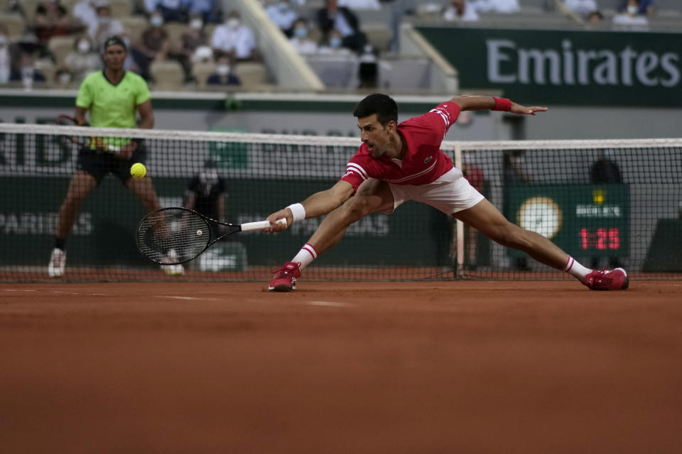 Serbia's Novak Djokovic stretches to return the ball to Spain's Rafael Nadal during their semifinal match of the French Open tennis tournament at the Roland Garros stadium Friday, June 11, 2021 in Paris. (AP Photo/Christophe Ena)