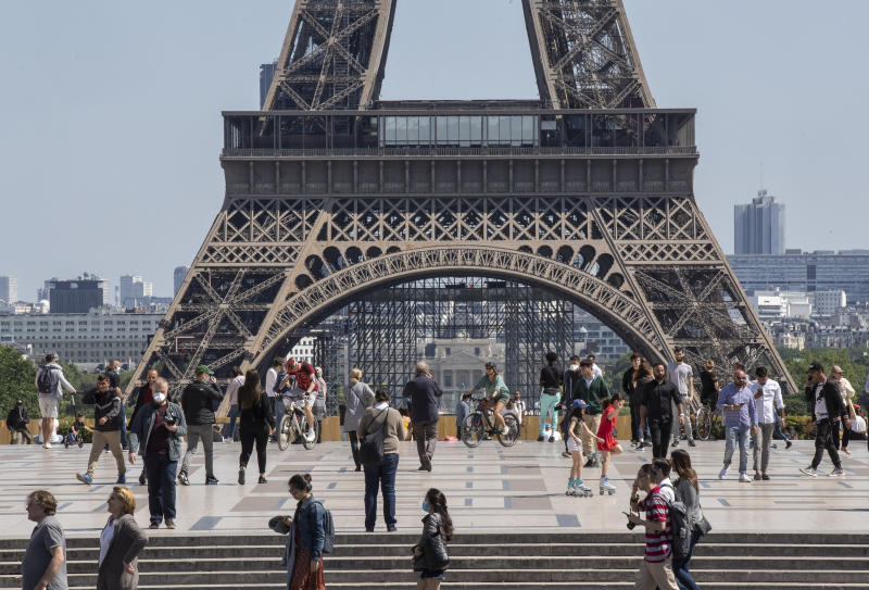 People stroll at Trocadero square next to the Eiffel Tower in Paris, Sunday, May 17, 2020 as France gradually lifts its Covid-19 lockdown. Parisians enjoying their first weekend in the sun since travel and movement restrictions were partially lifted. (AP Photo/Michel Euler)