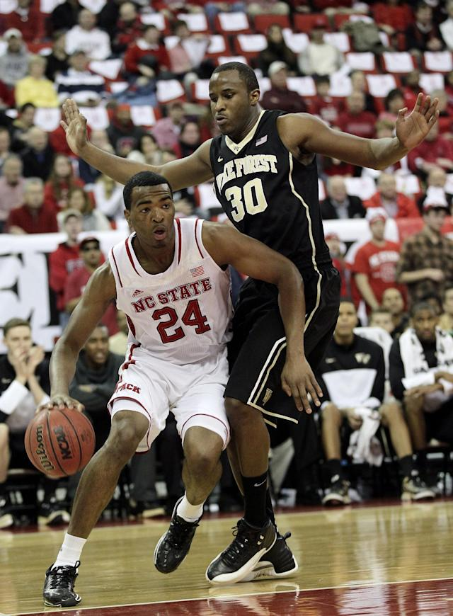 North Carolina State's T.J. Warren (24) drives to the basket as Wake Forest's Travis McKie (30) defends during the first half of an NCAA college basketball game in Raleigh, N.C., Tuesday, Feb. 11, 2014. (AP Photo/Gerry Broome)