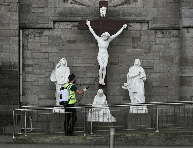 A man spraying disinfectant at a statue of the crucifixion of Jesus in Dublin on Good Friday.
