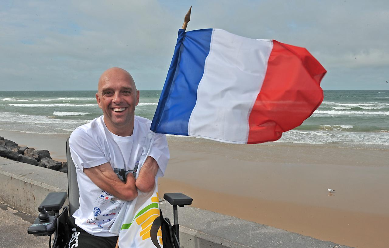TO GO WITH AFP STORY by Patrick Filleux (FILES) A file picture taken on September 20, 2010 shows French amputee and swimmer Philippe Croizon posing with a French flag in Wissant, northern France after he succeeded on September 18 his attempt to swim the English Channel, a challenge he has been preparing for two years. A Frenchman who gained fame for swimming the English Channel with no arms or legs has set himself a new challenge: to cross five continents in waters marked by sharks, poisonous jellyfish, icy currents and cargo ships. Philippe Croizon, 43, who lost both his arms and legs in an electrical accident 17 years ago, has begun preparing on May 2011, one year ahead to swim hundreds of kilometres in waters connecting five continents from May to August. AFP PHOTO / PHILIPPE HUGUEN (Photo credit should read PHILIPPE HUGUEN/AFP/Getty Images)