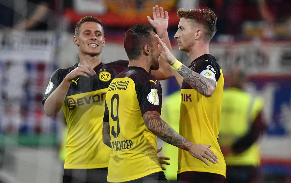 Dortmund's scorer Marco Reus, right, celebrates his opening goal with teammates Paco Alcacer and Thorgan Hazard during the German soccer cup, DFB Pokal, first Round match between KFC Uerdingen 05 and Borussia Dortmund in Duesseldorf, Germany, Friday, Aug.9, 2019. (AP Photo/Martin Meissner)