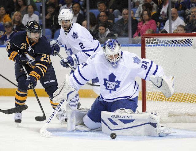 Buffalo Sabres' Ville Leino (23) looks for a rebound from Toronto Maple Leafs goalie James Reimer (34) as Leafs' Mark Fraser (2) defends during first period of an NHL hockey preseason game in Buffalo, N.Y., Saturday, Sept. 21, 2013. (AP Photo/Gary Wiepert)