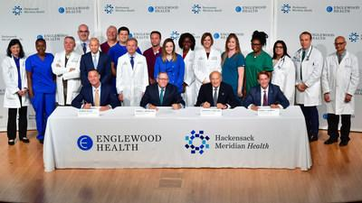 Warren Geller, president and CEO, Englewood Health; Thomas C. Senter, Esq., chairman, Board of Trustees, Englewood Health; Gordon N. Litwin, Esq., chairman, Board of Trustees, Hackensack MeridianHealth; and Robert C. Garrett, FACHE, CEO, Hackensack Meridian Health. The two health care systems have signed a definitive agreement to merge. Also pictured are physicians, nurses, and other clinical staff from Englewood Health and Hackensack MeridianHealth.