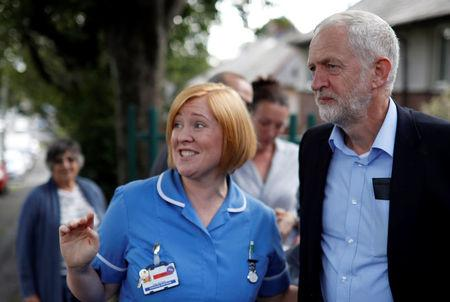 Britain's opposition Labour party leader, Jeremy Corbyn, speaks to a nurse during a visit to the Hope Centre in Bolton, Britain August 17, 2017. REUTERS/Phil Noble